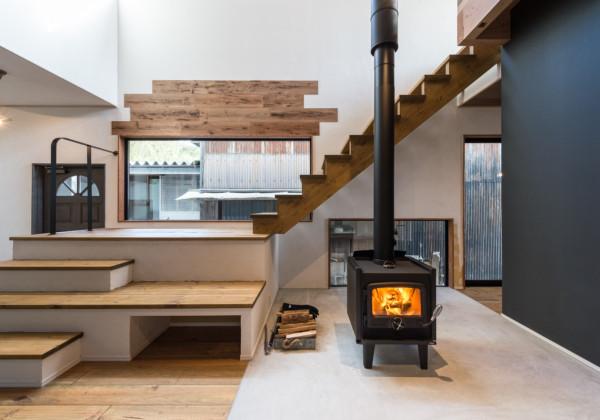 暖炉とひな壇階段のある家 1階に置かれた暖炉が家中を温めてくれます。暖炉のまわりに人が集えるよう、腰かけても使えるひな壇階段となっています。しっくい壁、床、天井、壁へのアクセントに貼られた無垢材と木をふんだんに使いそれぞれが時間とともに表情を変えていくのを楽しめるようなつくりになっています。 福岡工務店 福岡注文住宅建設 福岡注文住宅