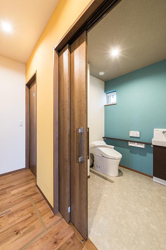 ゆったりスペースでリフォームいらず トイレの入口は二枚連動片引き戸。上から吊ってある戸なので、床面は段差などなく、スッキリ。トイレ内は車椅子の方の介助も楽々できるスペースを確保。便器右横には使わない時には跳ね上げておける手すりも設置されています。将来を見据えて家づくりすることで、将来の出費が抑えられます。 福岡工務店 福岡注文住宅建設 福岡注文住宅