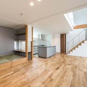 階段スペース利用で更に広々空間を確保した家 梁を見せながら、壁をつくらないことで階段周りの空間もリビングの一部にした事例。折り返し階段の踊り場下のスペースは収納、踊り場は本棚を置くことで家族の本が定位置管理ができるようになっています。和コーナーは腰掛けても使えるよう一段高くすることで椅子代わりとしても使用でき、また下部には収納ができるようになっています。キッチンに向かいカウンターを設置したことで、家事をしている親の側でお子さんが宿題をしたり会話したりといった使い方も可能です。 福岡工務店 福岡注文住宅建設 福岡注文住宅