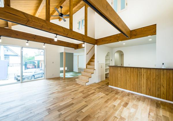 下の階にも上の階にも心地いい風の吹き抜ける梁見せ天井の家 こだわりのアーチ型入口のある壁はシンプルでありながらも独特の風合いを味わえる塗り壁となっています。リビングから見える2階の室内窓。2階から階下のリビングが見下ろせるだけでなく、開けておくと空気の流れも生まれ、冷暖房の効率がアップします。 福岡工務店 福岡注文住宅建設 福岡注文住宅