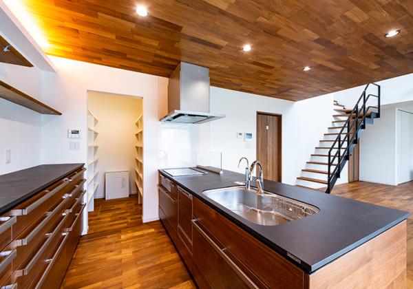 木のぬくもりを大切にした次世代住宅 従来のキッチンとは一線を画す、デザイン性のあるアイランドキッチン。優しい風合いが素敵なブラックウォールナット天然木突板扉に硬質なセラミックのワークトップと素材感抜群。スタイリッシュな家具として存在感のあるしつらえとなっています。ダイニングキッチンの天井には床材と同じチークを使用しており、建具などのトーンも合わせることで重厚感のある空間に仕上がです。間接照明を施すことで空間のアクセントとなっています。 福岡工務店 福岡注文住宅建設 福岡注文住宅