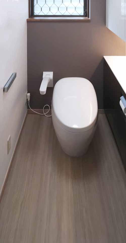 トイレリフォーム(福岡市東区 I様邸) 冬場の寒さ対策として赤外線ヒーターを使用されていたお施主様。トイレ内コンセントからヒーターまでの長い延長コードが視界に入るので気になります。隣接の洗面所から暖気・冷気を引き込むことで床が広く使えるだけでなく、視界に入っていたコードもなくなりスッキリした暖かい空間となりました。築36年のトイレは、便器の機能向上や節水効果を考え新しいタイプの最上位機種であるネオレストNXに交換。体の衰えに備えアームレストを採用するとともに、今は必要ないけれど、将来的に必要になった時のために壁補強も施しました。収納も開き戸タイプから、少ないスペースで出し入れできる引き戸タイプのものに変更。上部のキャビネットは、座った時の目線の高さのより高い位置に底面を設定。それにより以前と変わらない幅でも、より広く感じることができます。やわらかな間接照明の光がモザイクタイルを貼った壁に表情を与えてくれ、落ち着きのある空間を演出してくれます。また、タイル貼りだった床は段差を解消したうえで、ニオイの発生を抑えてくれるだけでなく汚れが染み込まないハイドロセラに変更。お手入れは水拭きだけでOKと掃除も楽になり、清潔感あふれる上質なトイレ空間となりました。 福岡工務店 福岡注文住宅建設 福岡注文住宅