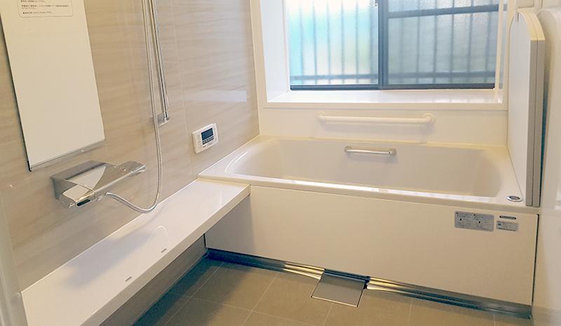ゆったりサイズ浴槽への変更リフォーム(福岡市南区 M様邸) タイル貼りの浴室にステンレスの浴槽。冬にはただでさえ寒い浴室が、それらのもつ質感によって更に厳しく感じるとのこと。そんな浴室が老朽化してきたので、何とかしたいとリフォームをお任せいただきました。足を伸ばして入れる浴槽のサイズを御希望のお施主様。ご希望を叶えるために決まった規格サイズのシステムバスではなく、サイズオーダーして既存の浴室にぴったり合わせ、無駄なくスペースが使えるタイプのものを選ばれました。ホーロー製の壁は、掃除が楽なだけでなくマグネット式のタオルかけや棚など思い通りの場所設置が可能です。高齢のお母様の安全性も考え、それまであった脱衣室からの10数センチの段差を無くしフラットにするとともに手すりも設置しました。 福岡工務店 福岡注文住宅建設 福岡注文住宅