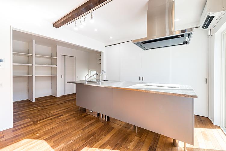 来客時にLDKにで目につくところはキッチン。 家電や調理器具といったものをどう収納するのかで見え方は違ってきます。 その1つめは、見せない収納。 料理器具などを表に出しておけば、使用する時にサッと使うことができ便利ですが 色数が多い場合や細々としたものが多いと雑然とした印象を与えてしまいます。 一方、すべてを扉の中に隠してしまうとスッキリ見えはしますが、 扉を開く→取り出す→使用 と使用する時に動作が1つ増えてしまいます。 使う時ごとに +1 は面倒です。そこで・・・ 使う時、見せたくない時だけ 扉を開閉できる仕様がおススメです。 キッチンの背面に大容量の背面収納を設けておくと いろいろなものを収納できるだけでなく、急な来客時も扉を閉めてしまえばOK!! 可動式の棚にしておけば、食器をはじめ日用品や本などどんなものでも そのサイズに合わせ収納することができます。 2つ目は、見えるタイプの収納を視覚に入らないように設置する方法です。 こちらの事例では奥まっている場所にあるため リビング側からは死角となり全く見えません。 視野に入れないこと・・・つまり 見えないものは認識されないので設置場所を工夫することでスッキリ見せることも可能です。 扉をつけない分、コストカットも可能です。 福岡工務店 福岡注文住宅建設 福岡注文住宅